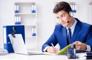 נציג שירות במחשב כותב עם עט ודף