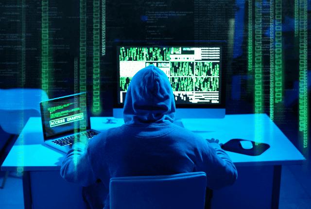 איש יושב ליד מחשב עם חומת אש במחשב